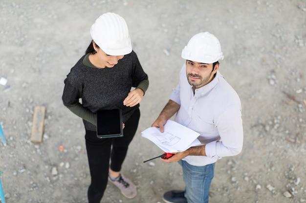 Bouwer en engineering op bouw bouwterrein kijken naar plannen bovenaanzicht