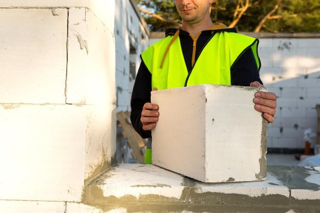 Bouwer houdt een blok cellenbeton in zijn handen - het metselwerk van de muren van het huis.