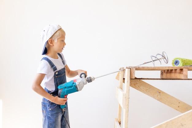 Bouwer houdt een bouwmixer tegen een witte muur en een bouwladder