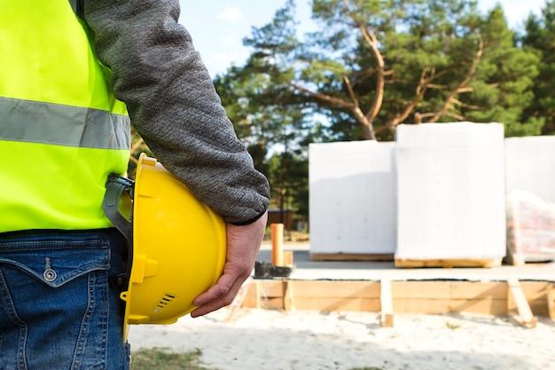 Bouwer houdt een gele beschermende veiligheidshelm in de hand op de bouwplaats