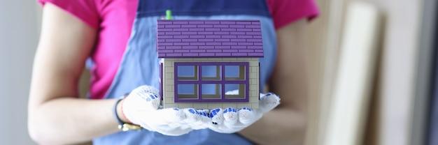 Bouwer houdt het huis in zijn handen. turnkey constructie van huizen concept