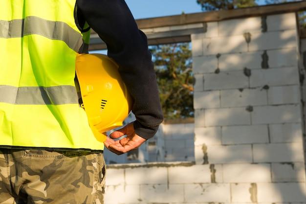 Bouwer houdt in de hand een gele beschermende veiligheidshelm op de bouwplaats met de fundering en muren van het huis gemaakt van cellenbetonblokken en bouwmaterialen. veiligheid op het werk, mockup