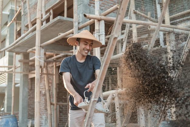 Bouwer houdt schop vast terwijl hij zand brengt om te zeven op strimin-draad tegen de achtergrond van de woningbouw