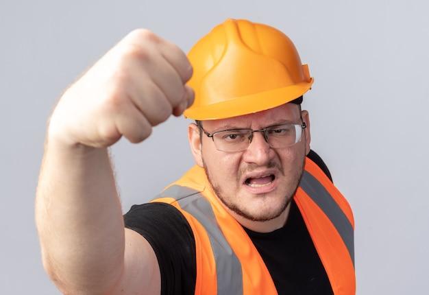 Bouwer in bouwvest en veiligheidshelm die naar camera kijkt met een boos gezicht met een vuist die over wit staat