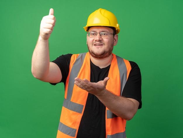Bouwer in bouwvest en veiligheidshelm die opzij kijkt, gelukkig en zelfverzekerd met de arm naar buiten en duimen omhoog