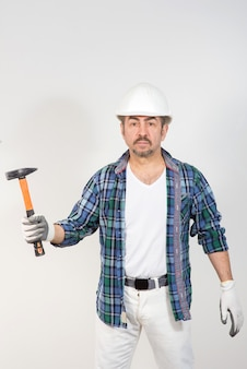Bouwer in een veiligheidshelm houdt een hamer tegen een witte muur