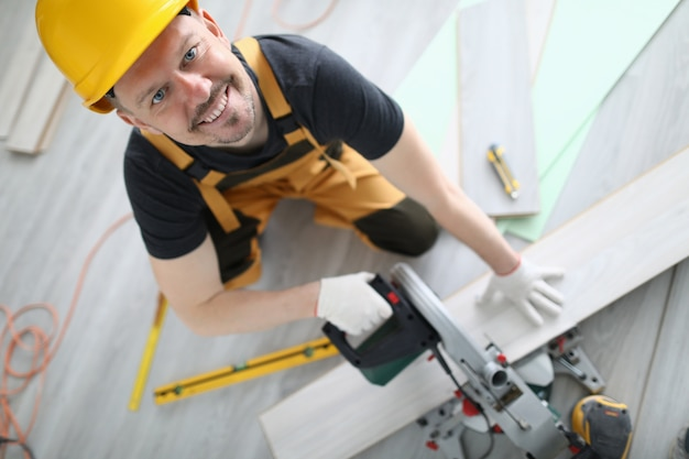 Bouwer in overall en helm gesneden laminaat op machine in kamer.