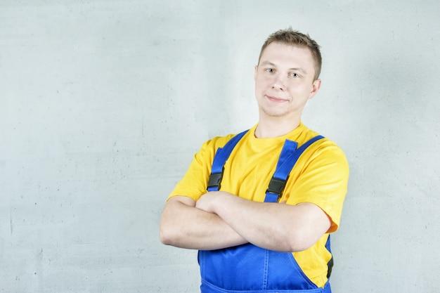 Bouwer in werkkleding tegen een grijze muur. de man sloeg zijn armen over zijn borst.