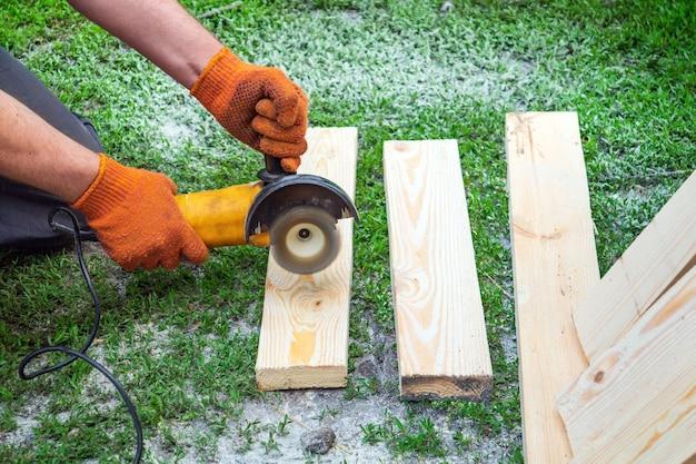 Bouwer maalt houten planken met een schuurgereedschap en slijpmachine