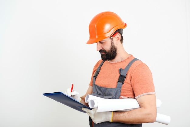 Bouwer maken van aantekeningen op klembord. professionele bouwer met veiligheidshelm. home renovatie. bebaarde knappe mannelijke bouwer.
