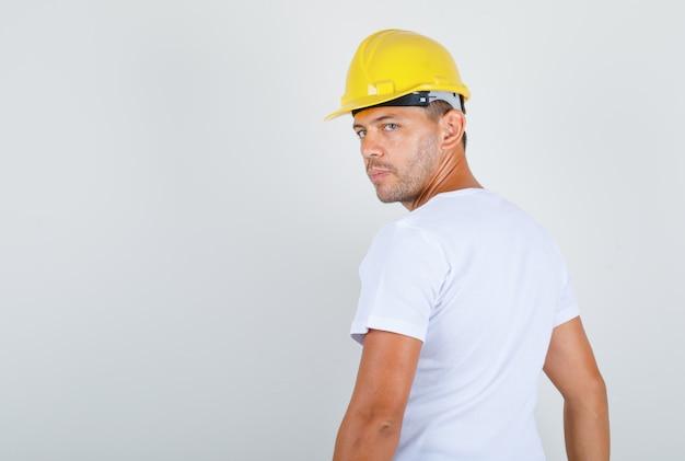 Bouwer man draaien en kijken achteruit in wit t-shirt, helm en op zoek naar ernstige, achteraanzicht.