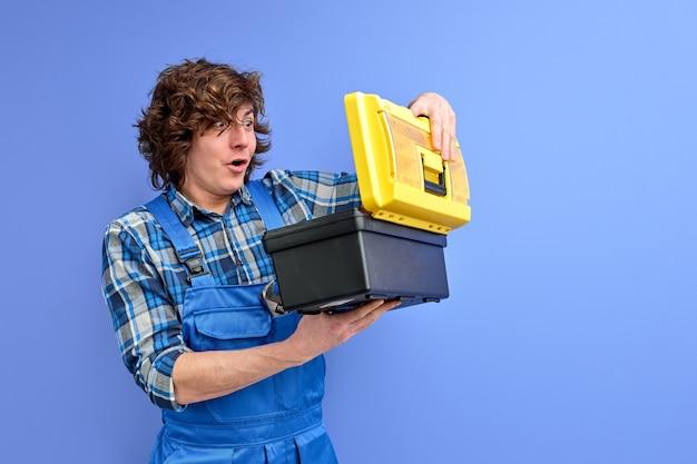 Bouwer man gereedschap doos openen met geschokt uitdrukking op het gezicht, gekrulde blanke man in blauwe overall geïsoleerd op paarse studio achtergrond.