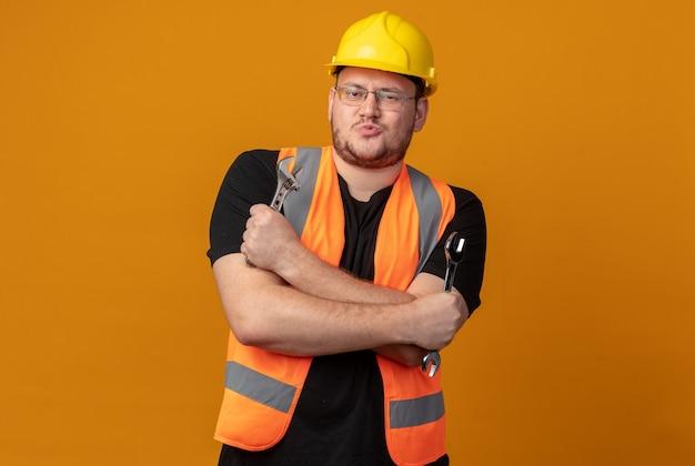 Bouwer man in bouwvest en veiligheidshelm met moersleutel kijkend naar camera met zelfverzekerde uitdrukking