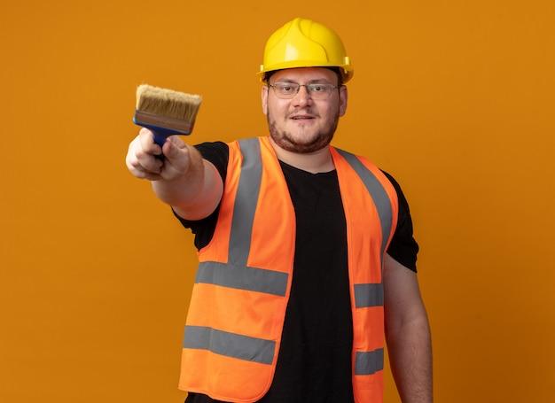 Bouwer man in bouwvest en veiligheidshelm met verfborstel kijkend naar camera met zelfverzekerde glimlach op gezicht staande over oranje achtergrond