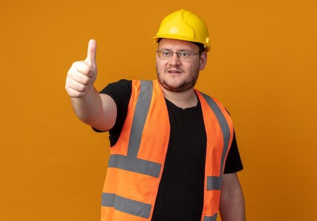 Bouwer man in bouwvest en veiligheidshelm opzij kijkend glimlachend zelfverzekerd met duimen omhoog staand over oranje achtergrond