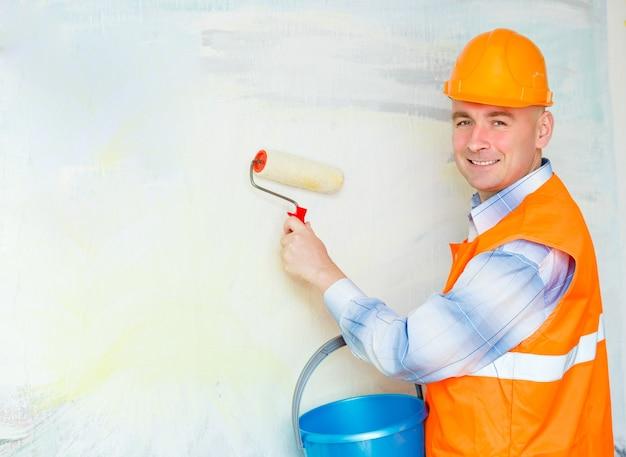 Bouwer man in een helm schildert de muur