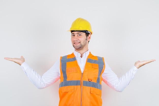 Bouwer man in shirt, uniform spreidende armen wijd als iets vangen en er gelukkig uitzien, vooraanzicht.