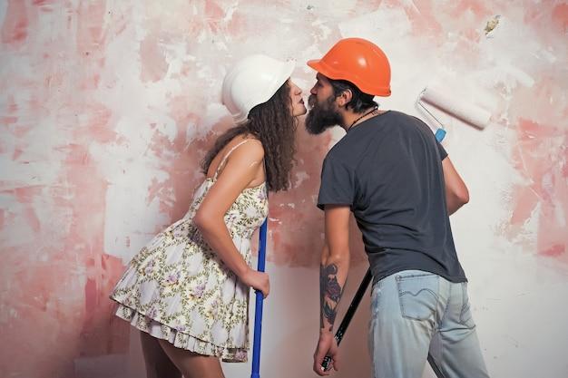 Bouwer man kus meisje in helm met gereedschap