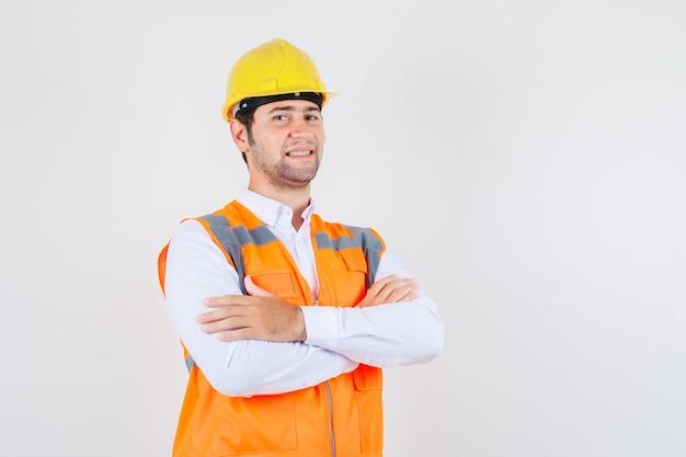 Bouwer man met gekruiste armen in shirt, uniform en op zoek naar kers. vooraanzicht.