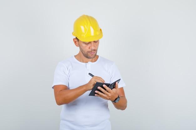 Bouwer man notities maken op mini notebook in wit t-shirt, helm en op zoek naar drukke, vooraanzicht