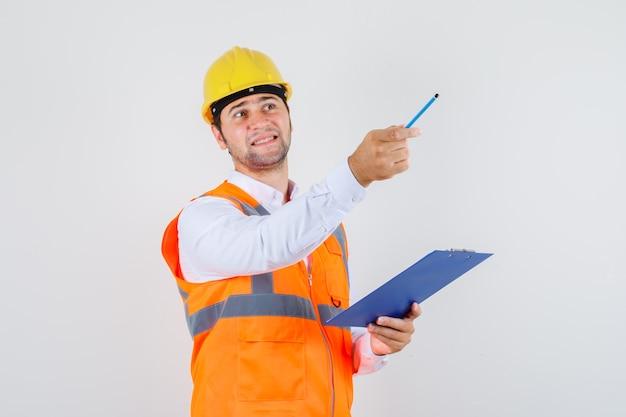Bouwer man wijst potlood weg terwijl klembord in shirt, uniform, vooraanzicht.