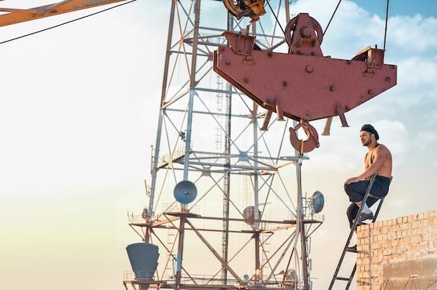 Bouwer met blote torso zittend op de ladder