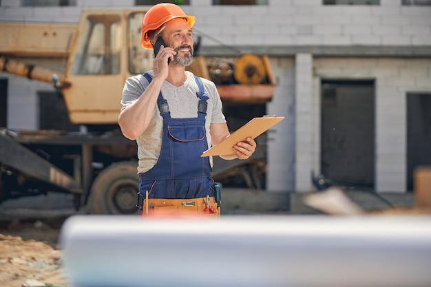 Bouwer met een klembord in zijn hand die een telefoongesprek voert