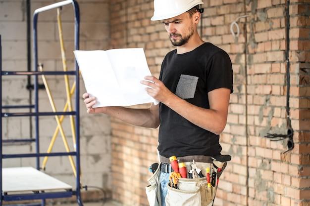 Bouwer met hulpmiddelen van de bouw op bouwplaats, blauwdruk kijken