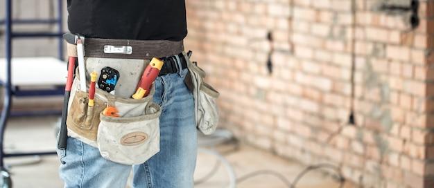 Bouwer met hulpmiddelen van de bouw op bouwplaats