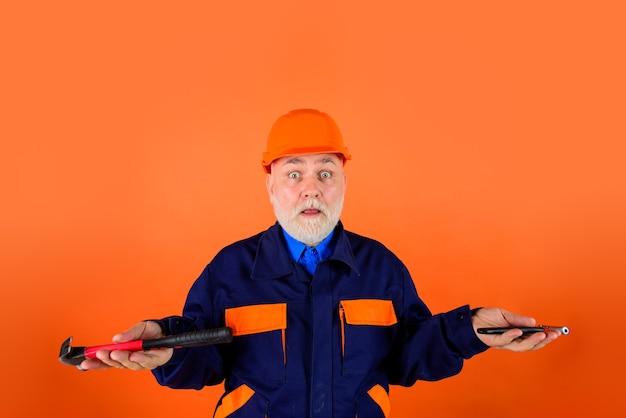 Bouwer met reparatietools bouwindustrie oude man in bouwhelm ingenieurs aan het werk