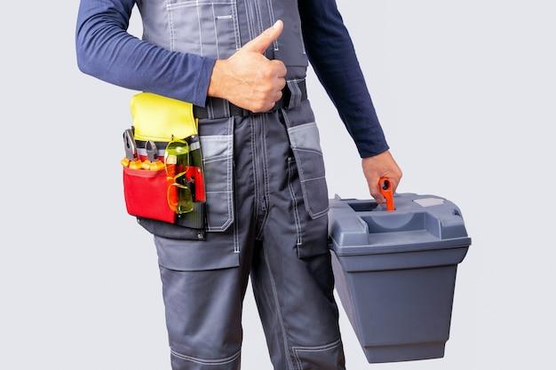 Bouwer met werkende hulpmiddelen in een doos die duim toont. hersteller met toolbox tegen grijze muur. dag van de arbeid concept.
