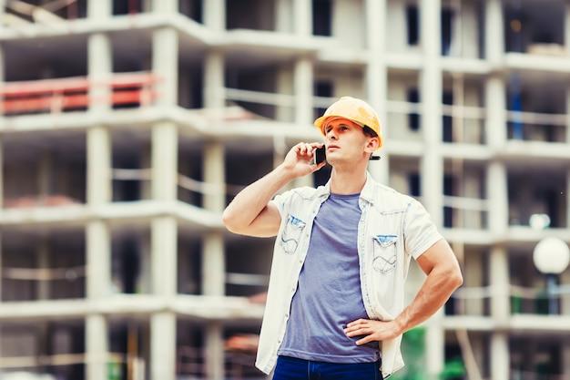 Bouwer op de bouwplaats praten mobilofoon