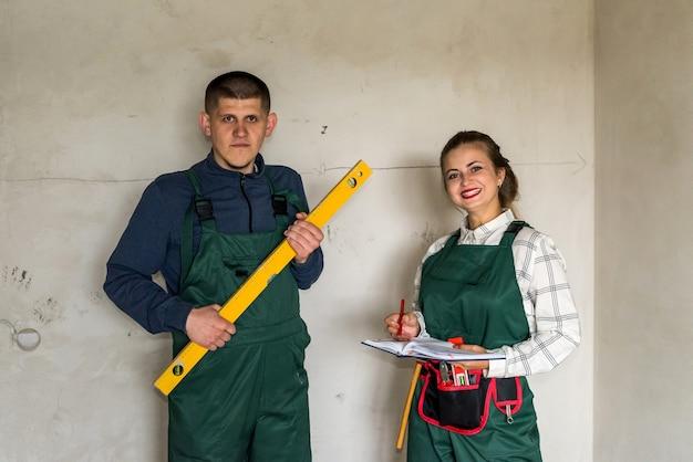 Bouwer poseren met waterniveau instrument en vrouw met notitieblok
