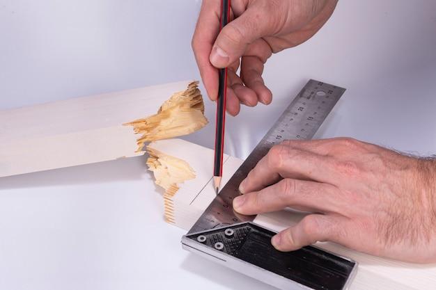 Bouwer trekt een lijn met een potlood op een gebroken bord voor reparatie, bouw van hout, bouw een huis