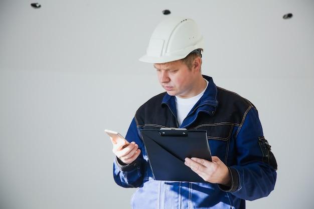 Bouwer voorman in een witte helm op een bouwplaats binnenshuis, plat renovatieconcept, professionele voorman op het werk met smartphone