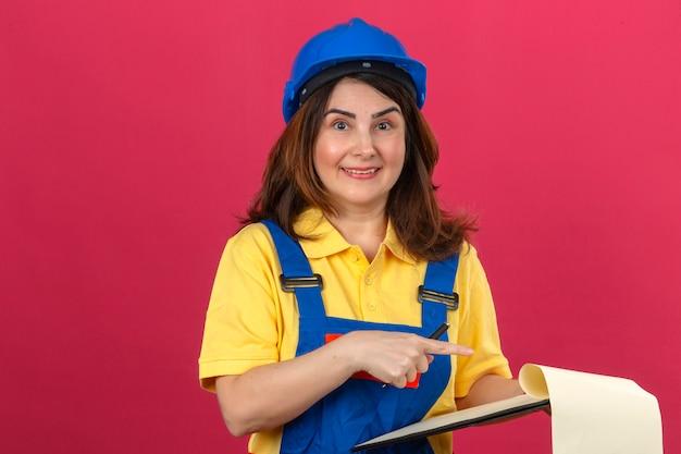 Bouwer vrouw uniforme bouw dragen en veiligheidshelm klembord en lege plekken te houden wijzen met de wijsvinger naar hen met een glimlach op zoek verrast over geïsoleerde roze backgr