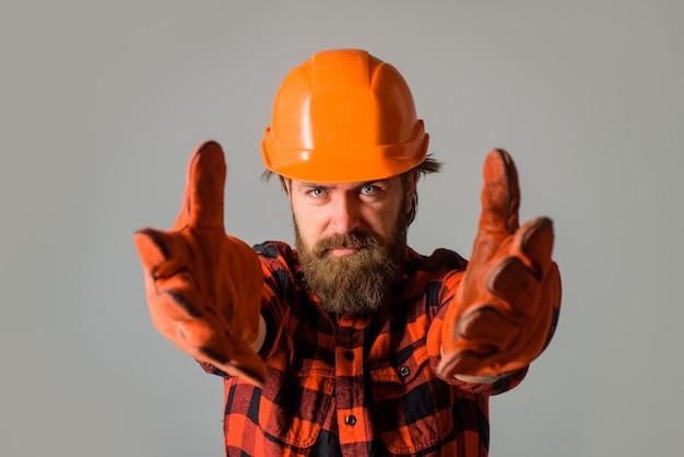 Bouwer werk bouwindustrie technologie bouwer in bouwvakker werkman in veiligheidshelm en werkhandschoenen