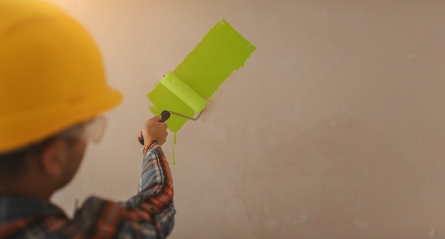 Bouwer werkt op de bouwplaats en meet het plafond. werknemer in een oranje helm en een verfroller schildert de muur.