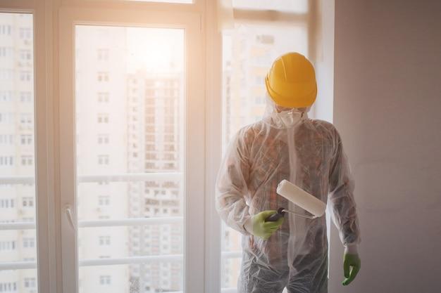 Bouwer werkt op de bouwplaats. werknemer met emmer en verfroller in de buurt van muur.