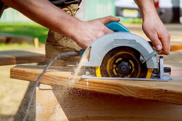 Bouwer zaagt een bord met een cirkelzaag die een houten plank snijdt