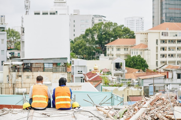 Bouwers in fel oranje vesten zittend op het dak van het gebouw in aanbouw en kijken naar de stad, uitzicht vanaf de achterkant