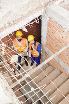 Bouwers met tabletcomputer staan op trappen in gebouw in aanbouw, praten over walkietalkie en kijken omhoog