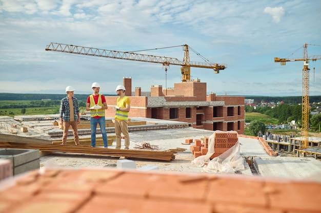 Bouwers met veiligheidshelm in gesprek met een ingenieur op de bouwplaats