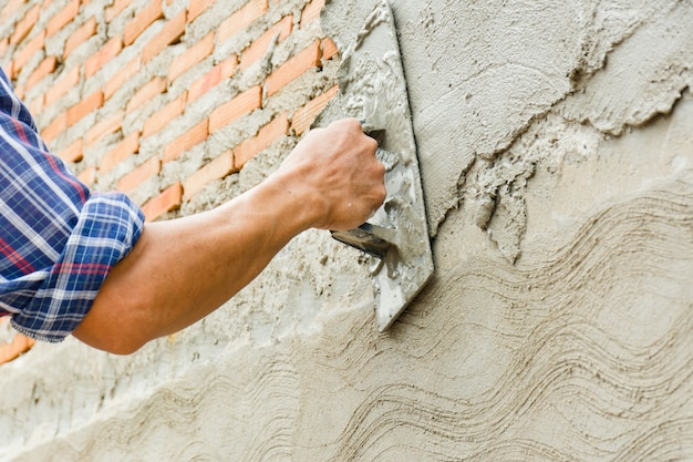 Bouwers pleisteren de muren van het huis netjes.