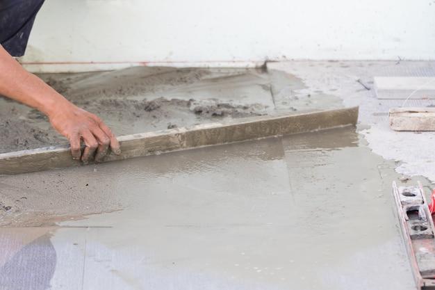 Bouwersarbeider bepleisteringsbeton bij vloer