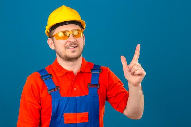 Bouwersmens die bouw eenvormige glazen dragen en veiligheidshelm die omhoog richtend met vinger kijken die nieuw idee hebben die zich over geïsoleerde blauwe muur bevinden