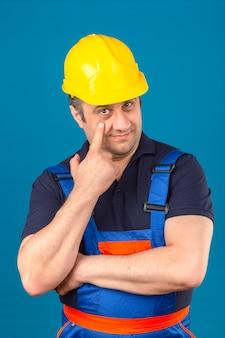 Bouwersmens die eenvormige bouw dragen en veiligheidshelm die aan het oog richten die op u gebaar verdachte uitdrukking over geïsoleerde blauwe muur letten