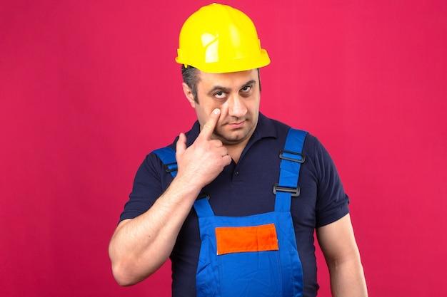 Bouwersmens die eenvormige bouw dragen en veiligheidshelm die aan het oog richten die op u gebaar verdachte uitdrukking over geïsoleerde roze muur letten
