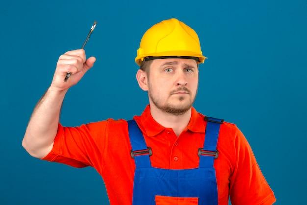 Bouwersmens die eenvormige bouw dragen en veiligheidshelm die dreigen te raken met moersleutel die ernstig over geïsoleerde oranje muur kijken