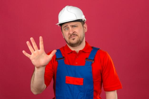 Bouwersmens die eenvormige bouw dragen en veiligheidshelm die en met vingers nummer vijf tonen tonen met sceptische uitdrukking op gezicht over geïsoleerde roze muur
